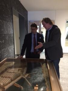 Wethouder Robert te Beest krijgt uitleg van Tom Hazenberg bij de maquette van fort Velsen 1 bij de rondleiding over tentoonstelling Romeinse Kust in het Huis van Hilde.